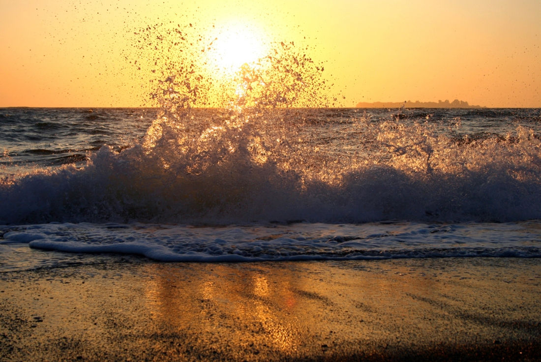 waves crashing on a beach at sunset